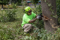 14-07-2020 - Flint, Michigan, USA, Flint Grounds Crew clearing growth from vacant lots with long abandoned houses nearly overgrown by trees and bushes © Jim West