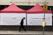 28-09-2020 - Man walking past Flu Vacination Clinic, NHS Surgery, Putney, London. Heathbridge Practice. © Duncan Phillips