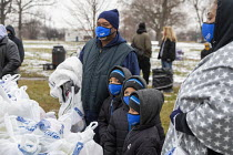 19-12-2020 - Detroit, USA Volunteers delivering food to people in need, in the week before Christmas, Roosevelt Park. Most of them homeless. A family with three young boys waiting in line to pick up food © Jim West