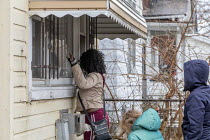 23-12-2020 - Detroit USA Tenant evicted for refusing landlord sex demands. Whitney Burney looks through the back window of her former home to see if any of her belongings remain. Burney and her four children had b... © Jim West