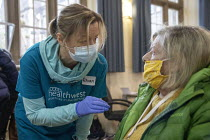 10-01-2021 - Pensioner receiving a Covid-19 Pfizer Vaccination, Clifton, Bristol. NHS Covid 19 Vaccination Service administering COVID-19 mRNA Vaccine BNT162b2 concentrate solution for injection, active immunisati... © Paul Box