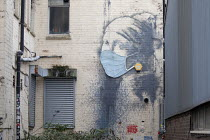 01-06-2021 - Coronavirus Pandemic. The Girl with a Pierced Eardrum by Banksy modified with a face mask added, Bristol Harbourside. Parody of The Girl With The Pearl Earring by Dutch painter Johannes Vermeer © Paul Box