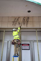 12-01-2021 - Workers boarding up closed H&M store, Covid lockdown. Bristol. The branch of clothing store H&M has closed permanently © Paul Box