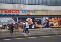 12-01-2021 - Tesco Metro, Broadmead, Bristol. Pedestrians in masks walking past advertismants for eggs and baking croissants © Paul Box