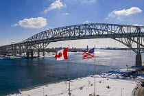 20-02-2021 - Port Huron, Michigan, USA: American and Canadian flags flying at The Blue Water Bridge connecting the USA (R) and Canada over the St. Clair River © Jim West