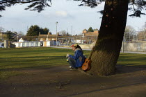 11-02-2021 - Homeless young man siting under a tree in the Park, Bancroft Gardens, Stratford upon Avon, Wawickshire © John Harris