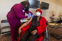 27-02-2021 - Detroit, USA: Vaccination against the coronavirus, Detroit Health Department weekend community clinic. Elderly disabled African American woman receiving the Moderna vaccine © Jim West