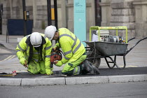 03-03-2021 - Workers repairing pavement during Covid pandemic lockdown, Piccadily, London. Working in close proximity outdoors © Jess Hurd