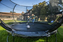 09-03-2021 - Brothers playing football on trampoline, Welford-on-Avon, Warwickshire © Paul Box