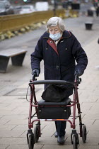 04-03-2021 - Elderly woman shopping with a half on face mask and walking mobility aid, Stratford upon Avon, Warwickshire © John Harris