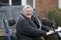 08-03-2021 - Smiling elderly man on the way to the shops on a motorized wheelchair, Stratford upon Avon, Warwickshire © John Harris