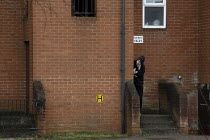 19-03-2021 - Youth on mobile phone, block of flats, Banbury © John Harris