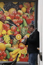 19-03-2021 - Man eating a bag of crisps in front of a fresh fruit advertisment, Banbury town centre © John Harris