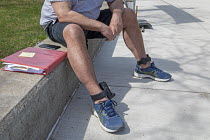10-04-2021 - Detroit, USA. Man wearing an electronic tether on each ankle. The devices report his location to criminal justice authorities. © Jim West